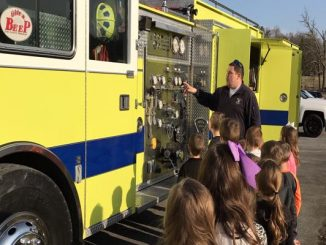 Students line up to look inside a fire truck during a visit to Lynn Camp Elementary.