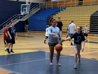 Girls are shown bouncing a basketball on the court with other players in the background.