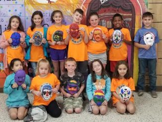 Students pose with face masks that they created during camp at Lay.