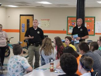 Sheriff Mike Smith and school resource officer Mike Broughton share safety tips with students during Lynn Camp's summer camp.