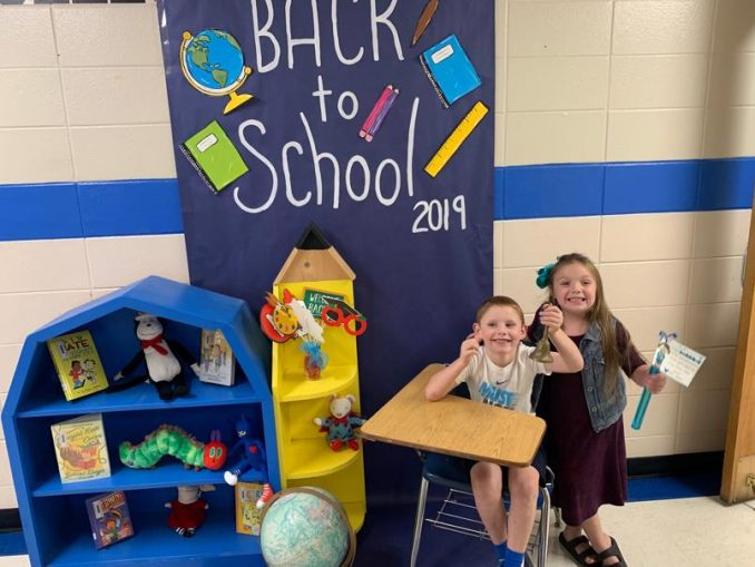 Students pose in front of a back to school decorated door and desk.