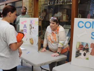 A student is shown visiting the community service display set up by Partner Corp members during RUSH week.