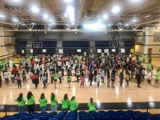 Link Crew members are shown on the gym floor introducing themselves to new freshman in groups.