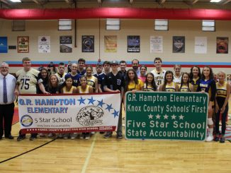 Banners and highway signs announced the 5 star rating of GR Hampton. Students and staff are posed on the gym floor holding the signage.