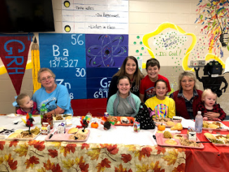 Students and family members pose behind the lunchroom table at GR Hampton for their family thanksgiving lunch.