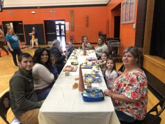 A family at Lynn Camp is shown with their students at the Thanksgiving lunch table.