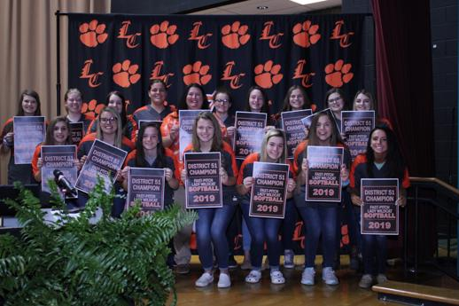 Lynn Camp Softball players pose in front of the LC backdrop celebrating their district win.