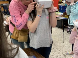 Davis is shown adjusting one students virtual reality headset.