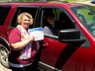 Teacher shown presenting certificate to student inside car.